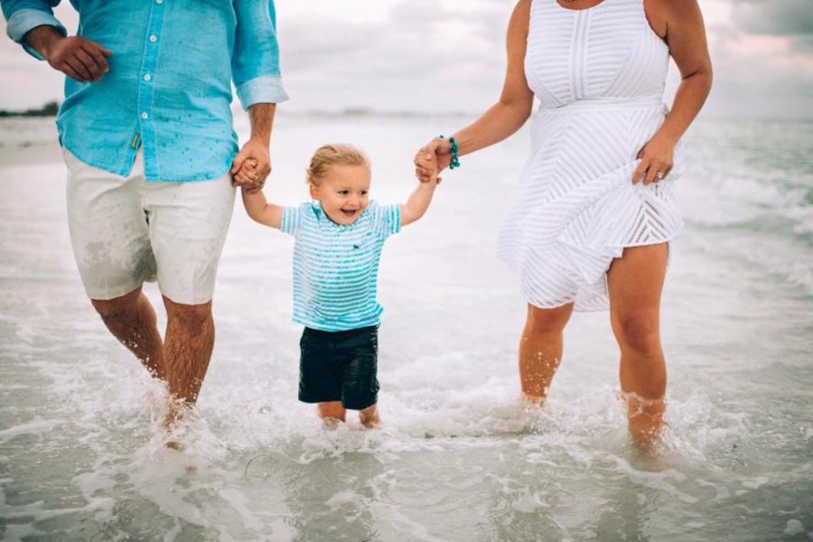 family of 3 walking in the ocean