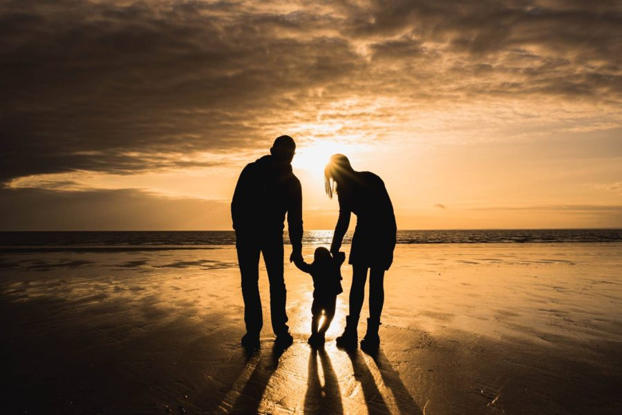 family of 3 walking during beach sunset