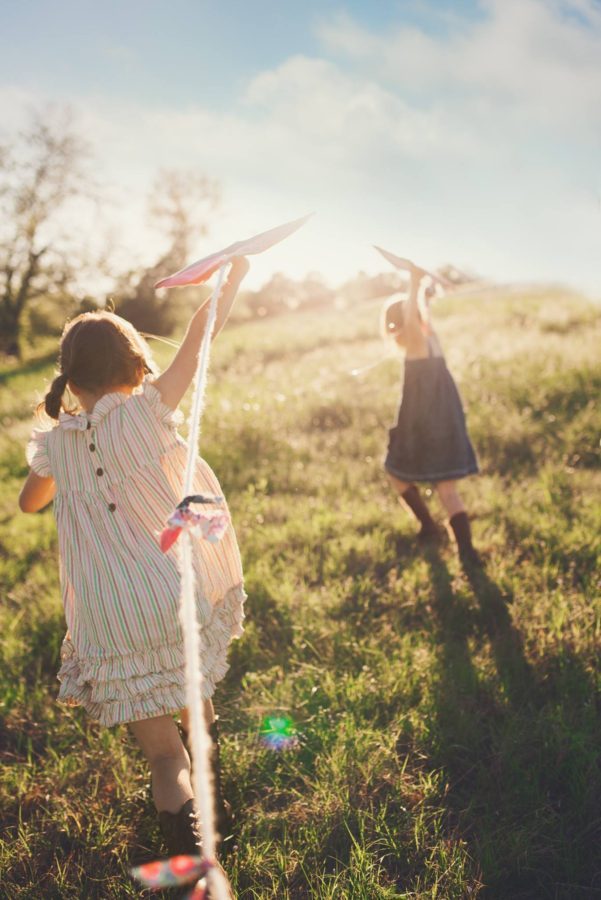 sister playing airplanes in field