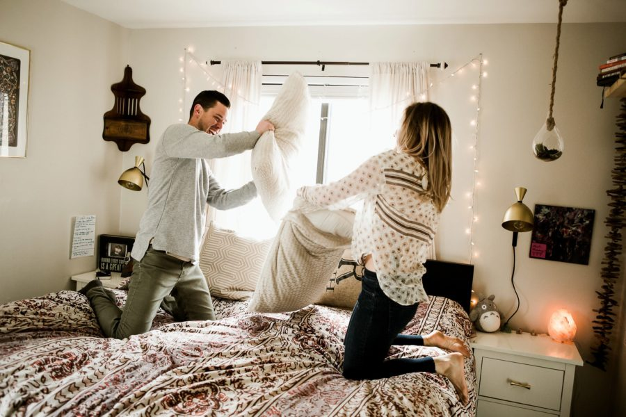 couple having pillow fight on bed, Romantic in Home Anniversary Session
