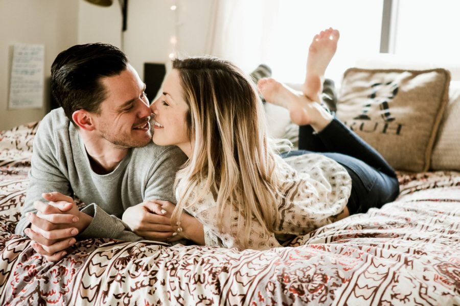 man and woman laying on bed smiling, Romantic in Home Anniversary Session