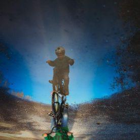 boy riding bike in puddle, daily fan favorite