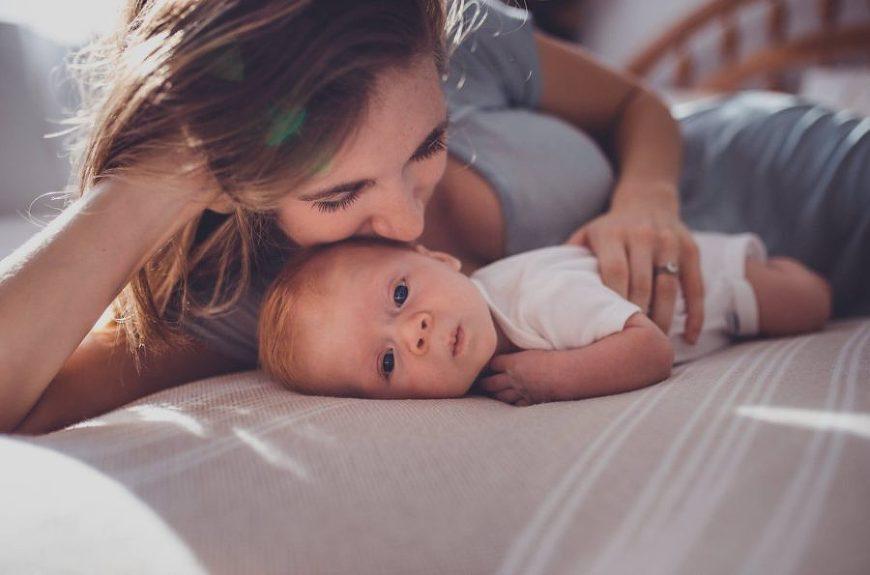 mom kissing newborn baby, daily fan favorite