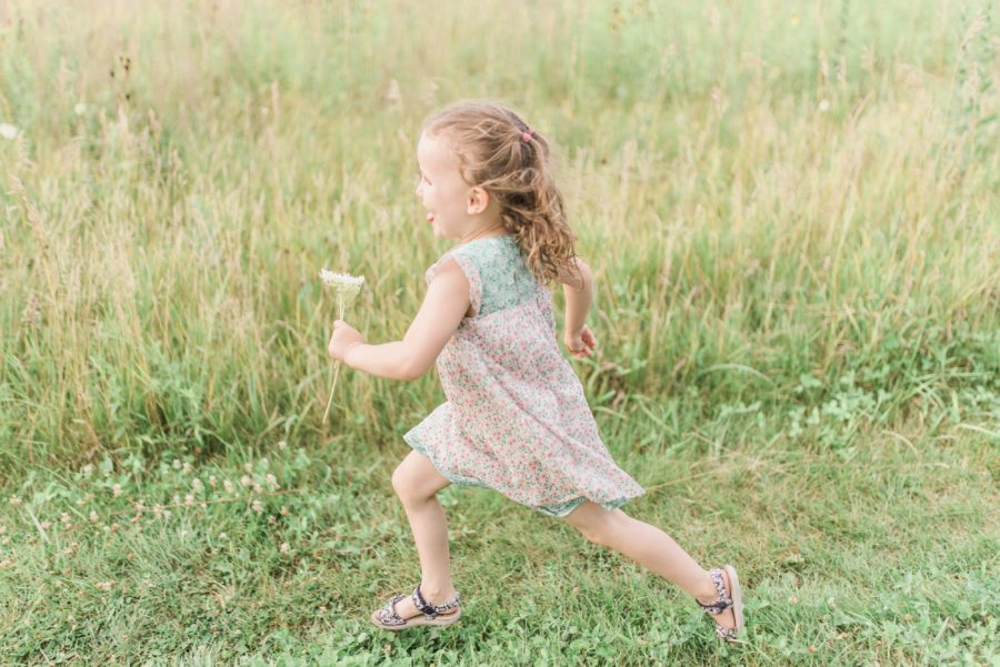 Girl running in field, Outdoor lifestyle session, Light-Drenched Family Portraits in Wisconsin