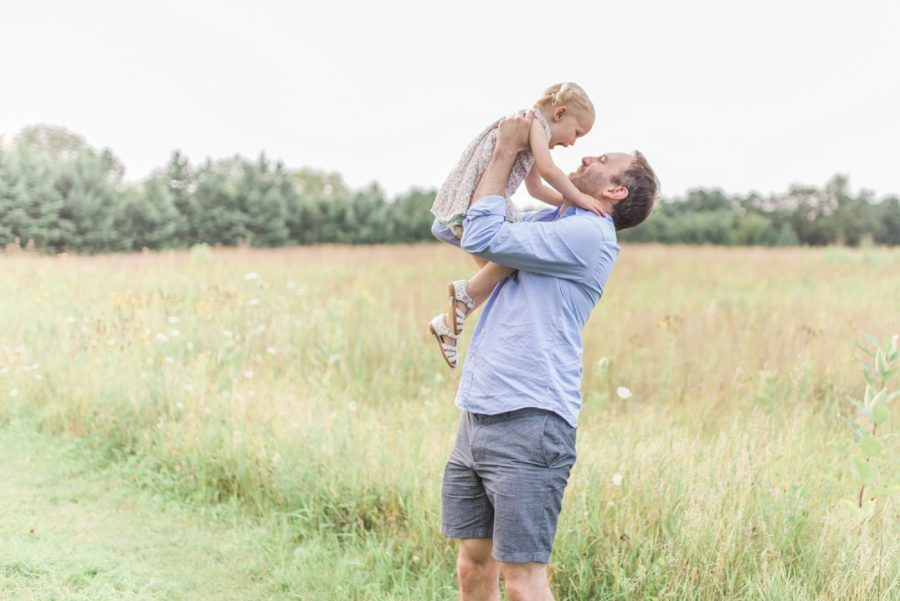 Father lifting up child, girl looking at daddy, Light-Drenched Family Portraits in Wisconsin