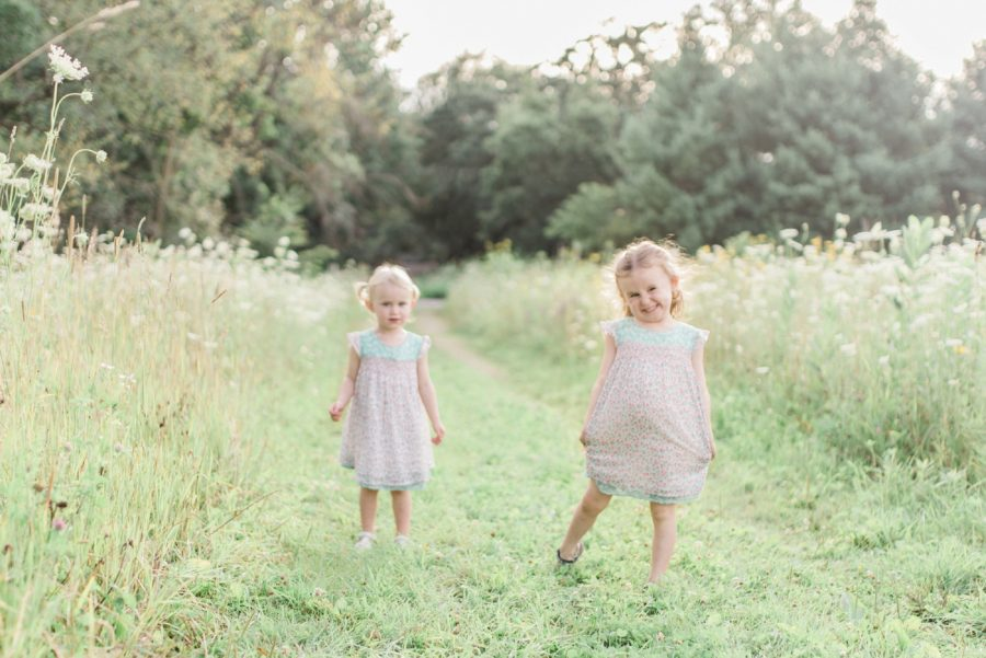 Sisters in wildflower field, Girl smiling, Light-Drenched Family Portraits in Wisconsin