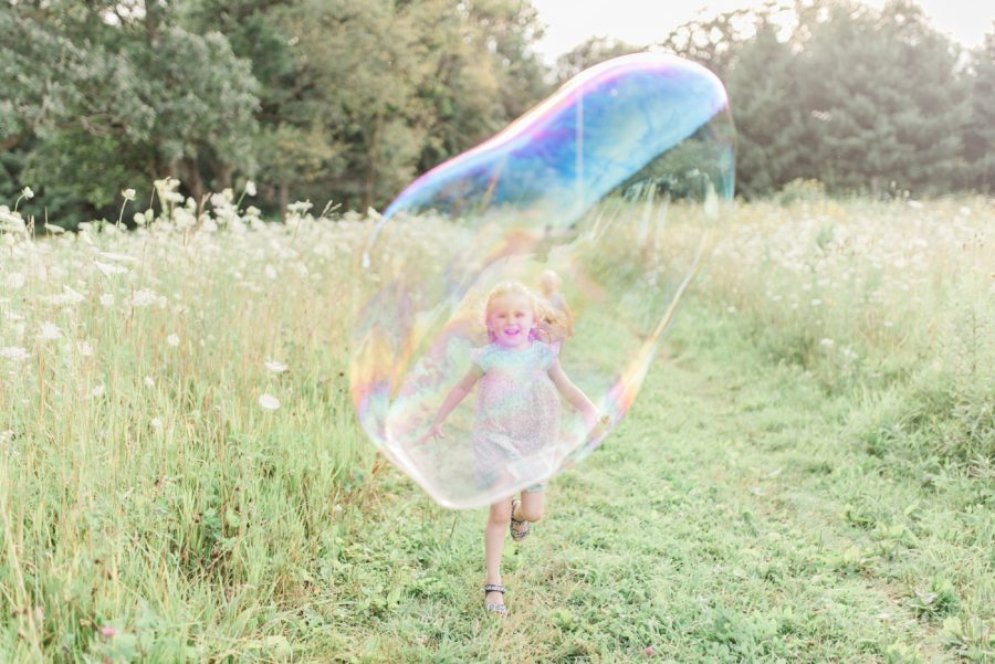 Girl chasing bubbles, bubbles, Light-Drenched Family Portraits in Wisconsin