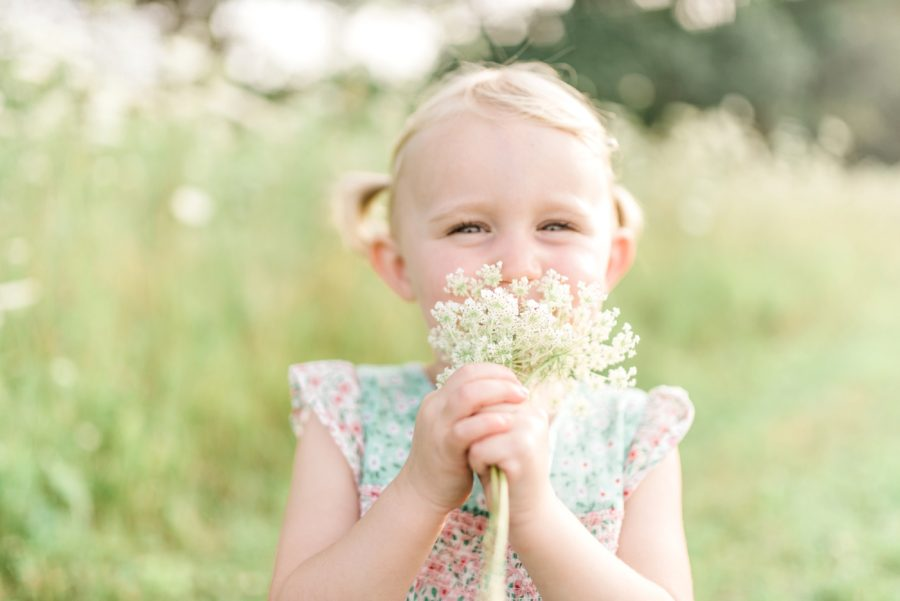 Girl smelling flowers, wildflowers, Light-Drenched Family Portraits in Wisconsin