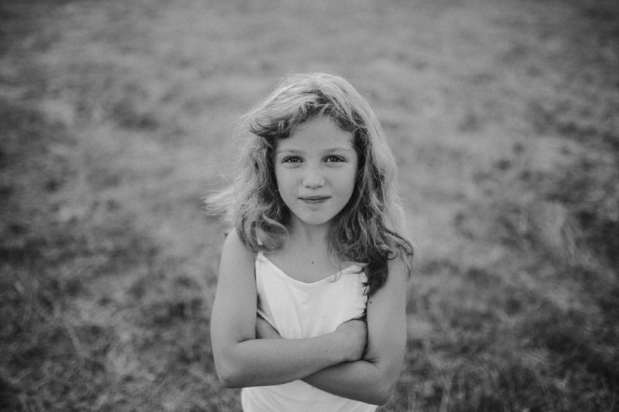 Girl looking at camera, arms crossed, Wild and Free Childhood Portraits