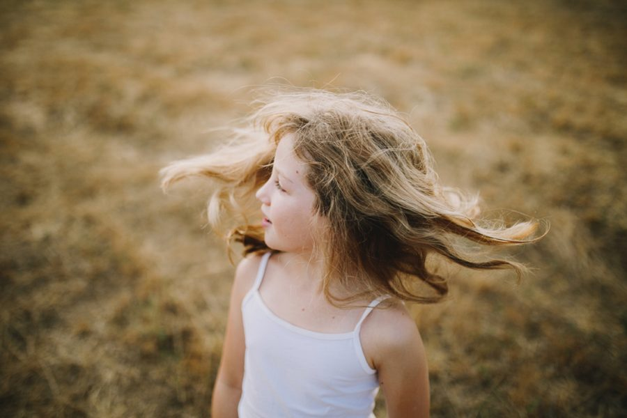child spinning, yellow grass, Wild and Free Childhood Portraits