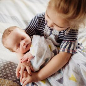 girl holding newborn, baby hands, daily fan favorite