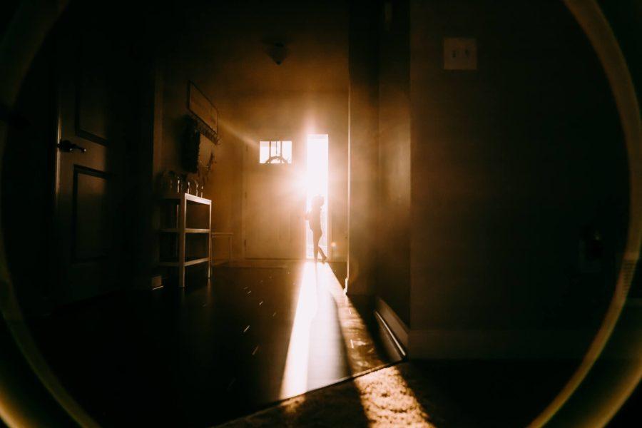 child opening front door, sun flare