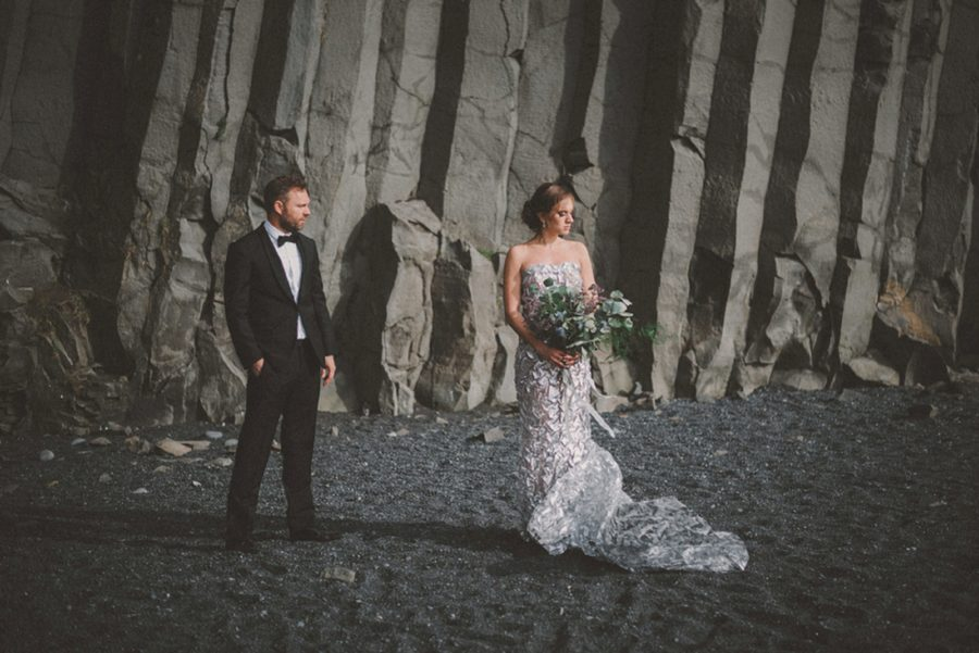 groom looking at bride, man and woman in front of rock wall, Styled Elopement Pictures in Iceland