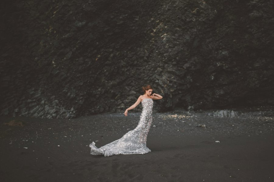 woman posing on black beach, black rocks in background, Styled Elopement Pictures in Iceland