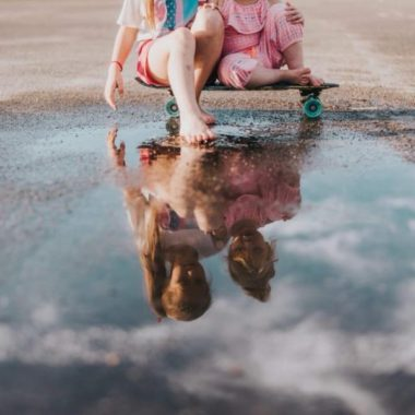 Two girls sitting on skateboard looking at reflection, puddle reflection image, Photos by Lindsey Daily Fan Favorite
