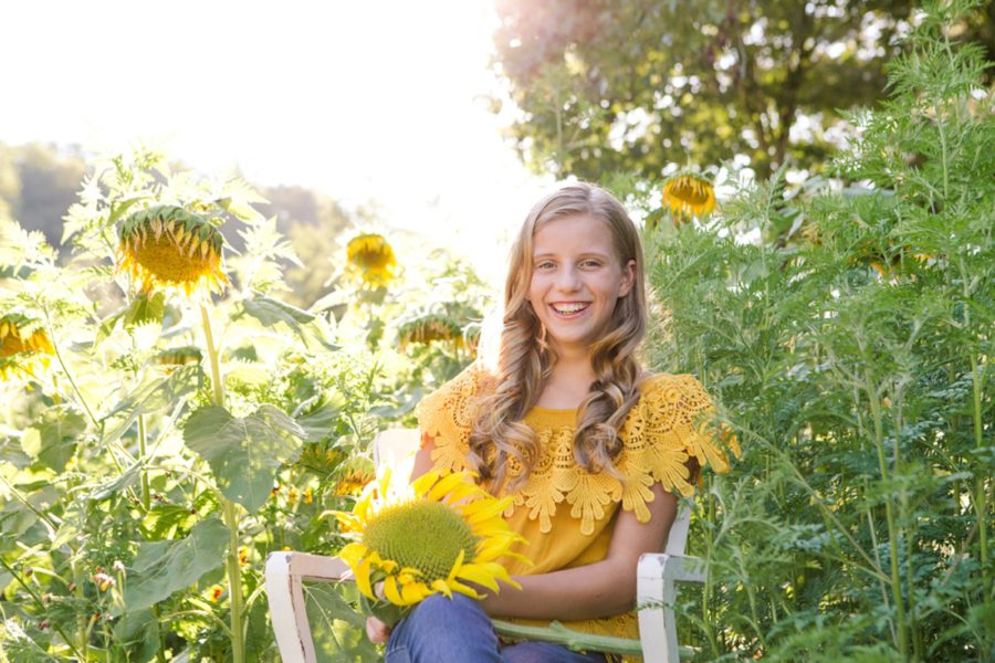 Girl sitting in chair surrounded by sunflowers, Sweet 13 Photo Session in North Carolina