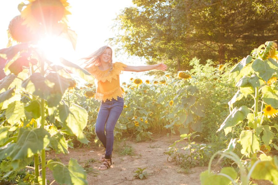 Girl twirling in sunflower field, girl with arms out in sunshine, Sweet 13 Photo Session in North Carolina