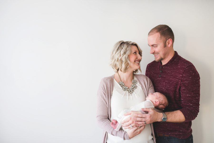 Couple looking at each other and holding newborn, Clean and Simple Newborn Portraits