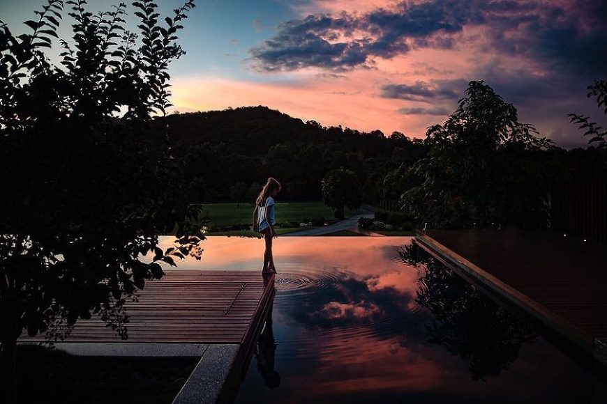 girl dipping toe into water, infinity pool, sunset, reflection of sunset, Daily Fan Favorite on Beyond the Wanderlust