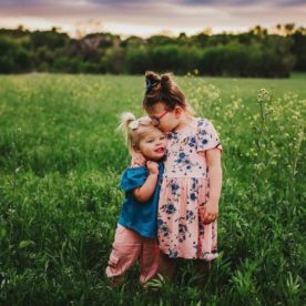 Portrait of sisters hugging in grassy field, Daily Fan Favorite on Beyond the Wanderlust