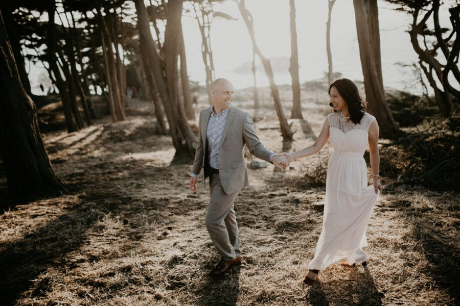 couple walking through wooded beach area, picture of man and woman holding hands and walking, San Francisco Beach Engagement Photos