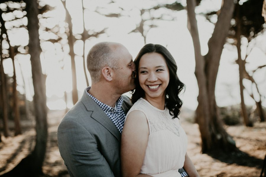 man kissing womans ear, portrait in trees, San Francisco Beach Engagement Photos