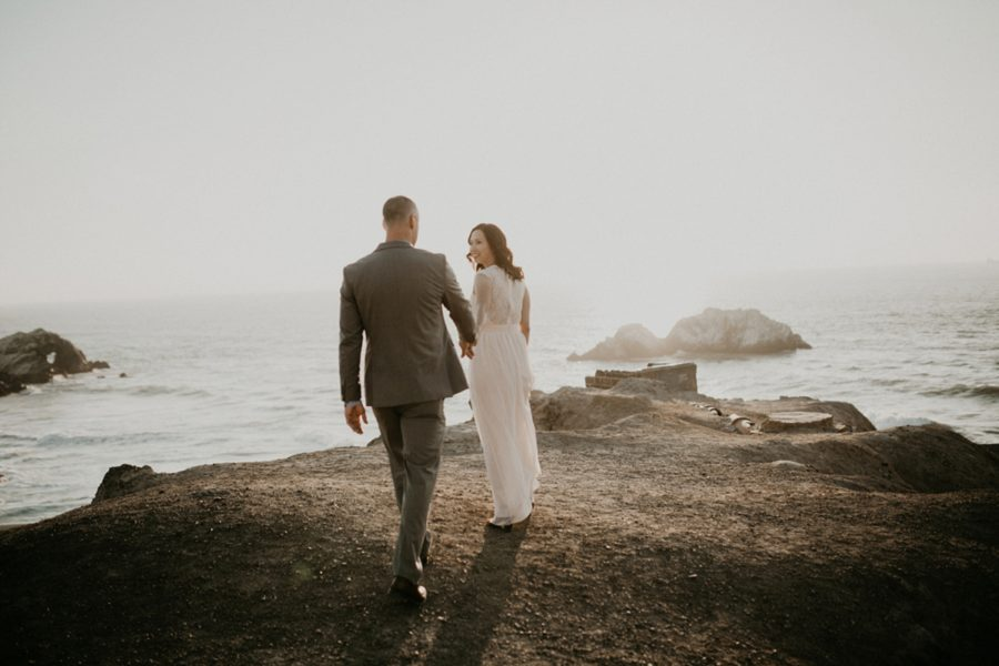 couple walking onto rocky pier, engagement photos by the sea, San Francisco Beach Engagement Photos