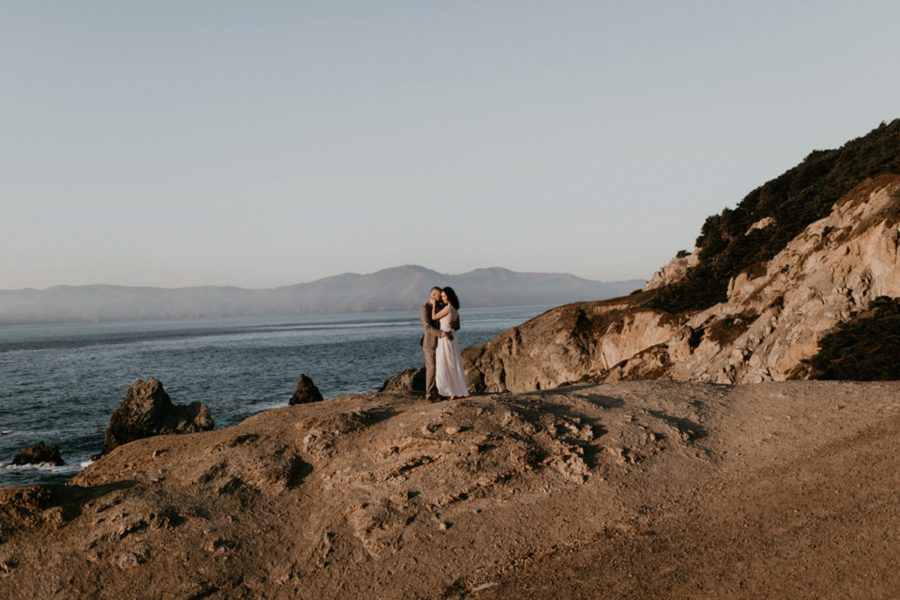 man and woman embracing on rocky beach, San Francisco Beach Engagement Photos