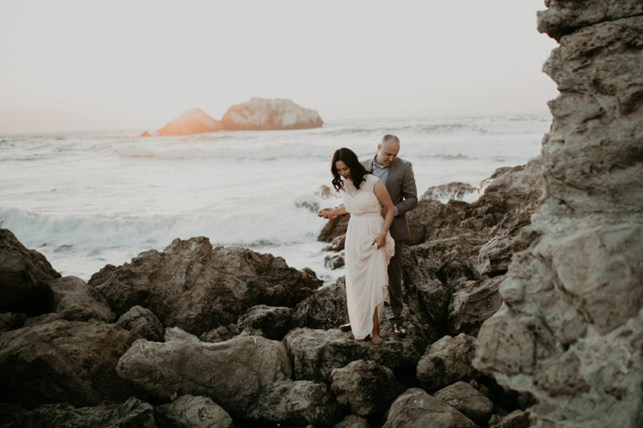 man helping woman walk on rocks, rocks by the ocean, San Francisco Beach Engagement Photos