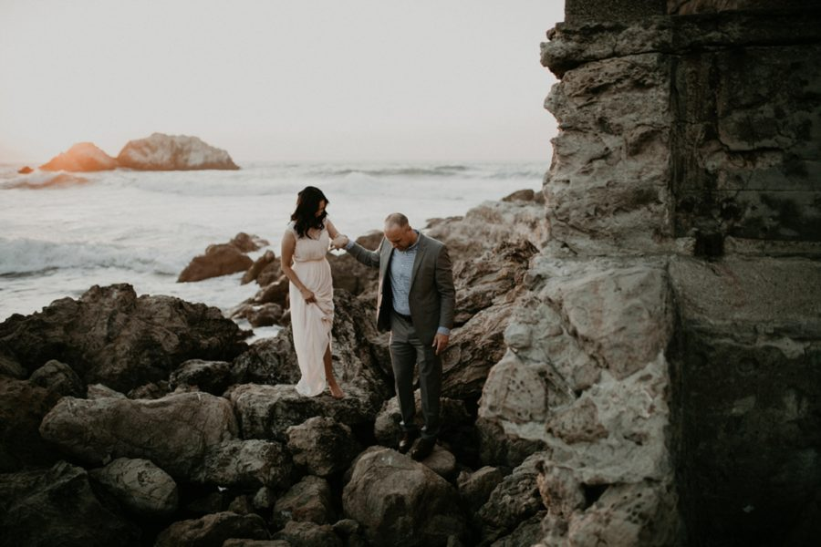 walking on rocks by the water, San Francisco Beach Engagement Photos