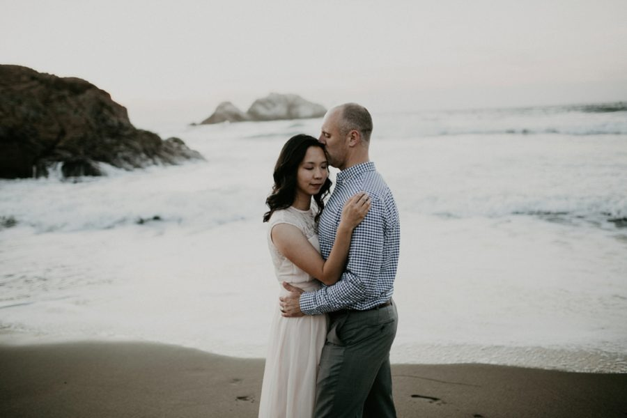 man and woman embracing in front of waves, sandy beach photos, San Francisco Beach Engagement Photos