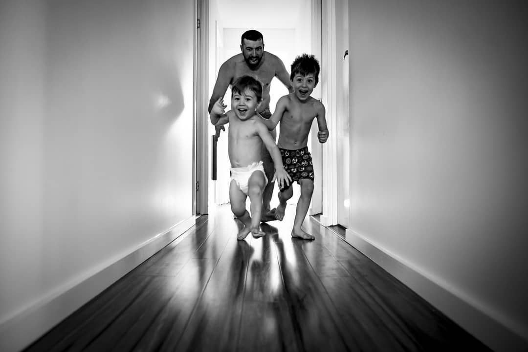 Dad playing chase with kids, boys running down hallway, Daily Fan Favorite
