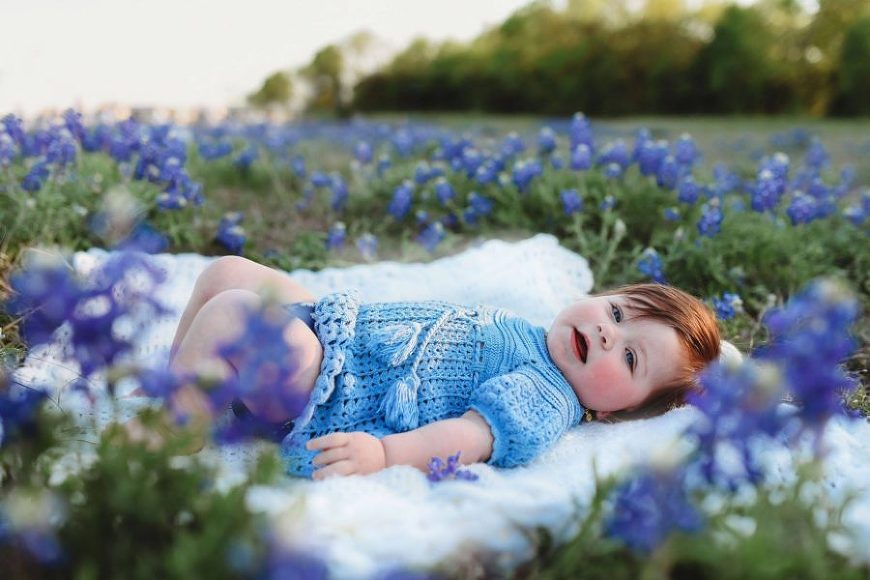 Baby lying in blue bonnet field, blue crochet baby outfit, Daily Fan favorite