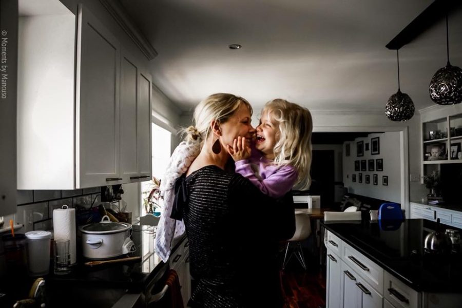 Mom laughing with daughter, mom holding girl in kitchen, Daily Fan Favorite on Beyond the Wanderlust