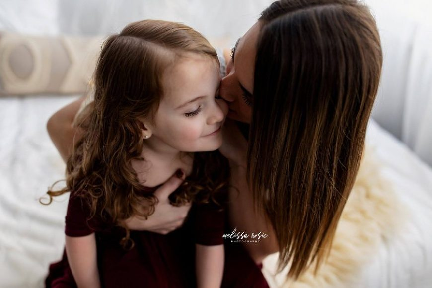 Woman kissing girls cheek, embrace between mother and daughter, Daily Fan Favorite on Beyond the Wanderlust