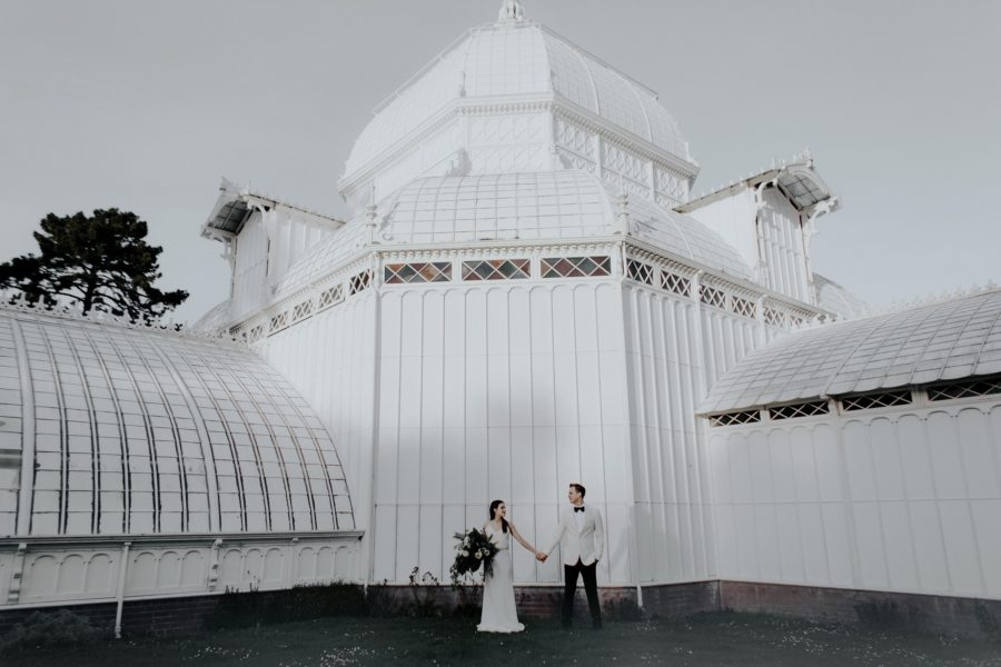 Couple holding hands in front of building, Portrait outside of Conservatory of Flowers, Edgy Styled Wedding Portraits in San Francisco
