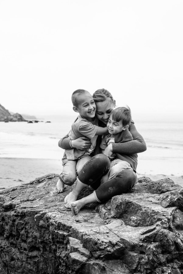 Portrait of boys with mom at beach, family sitting on rock in front of ocean, Daily Fan Favorite on Beyond the Wanderlust
