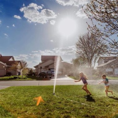 Children running through sprinkler on sunny day, Daily Fan Favorite on Beyond the Wanderlust by Wild Meadow Photography