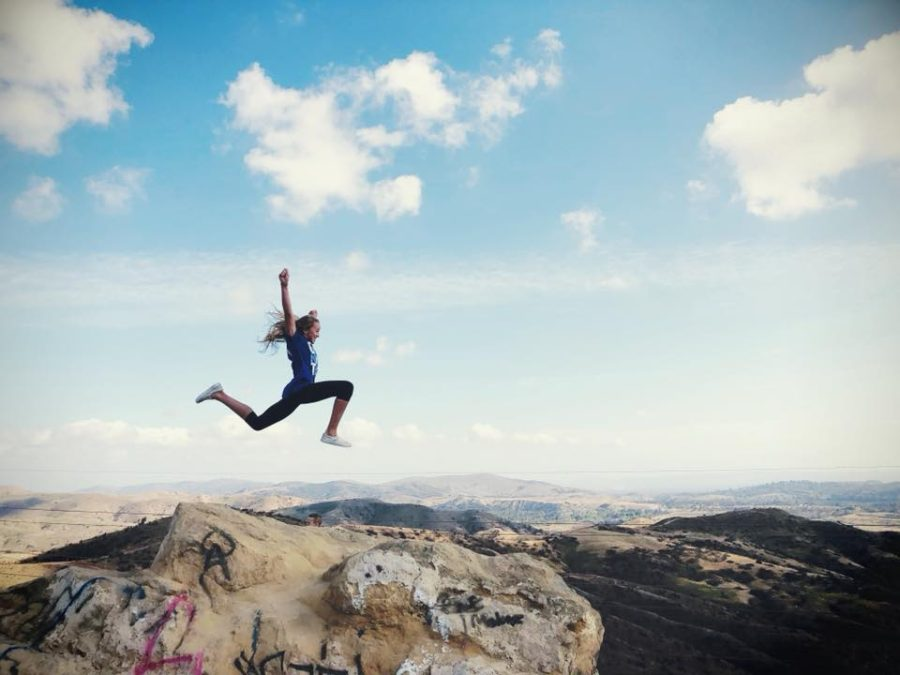 Girl jumping in to air with mountains in background, Beyond the Wanderlust Daily Fan Favorite