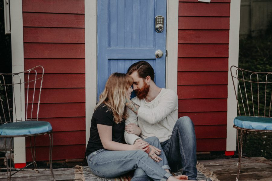 Man and woman sitting outside door of tiny home, Couple on porch together, Couples Lifestyle Session in North Carolina Tiny House