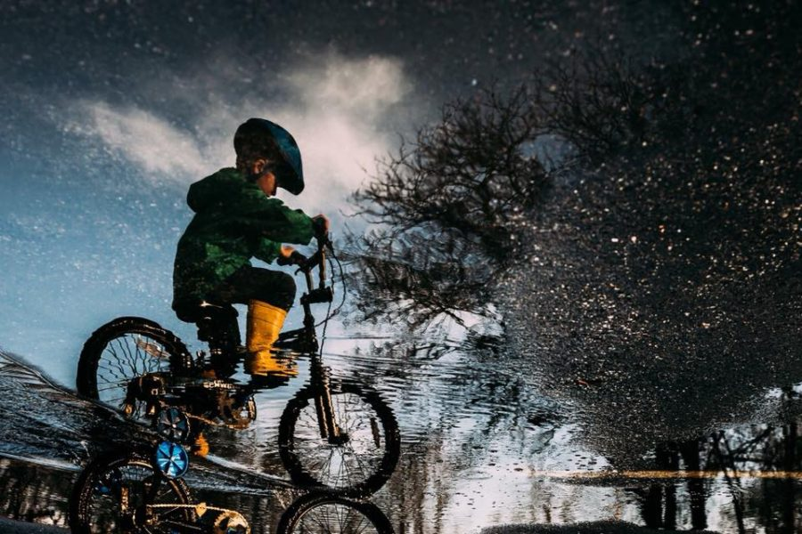 Reflection of child riding bike through puddle, upside down reflection picture, Beyond the Wanderlust Daily Fan Favorite