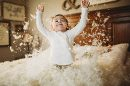 Child throwing feathers on bed, Beyond the Wanderlust Daily Fan Favorite