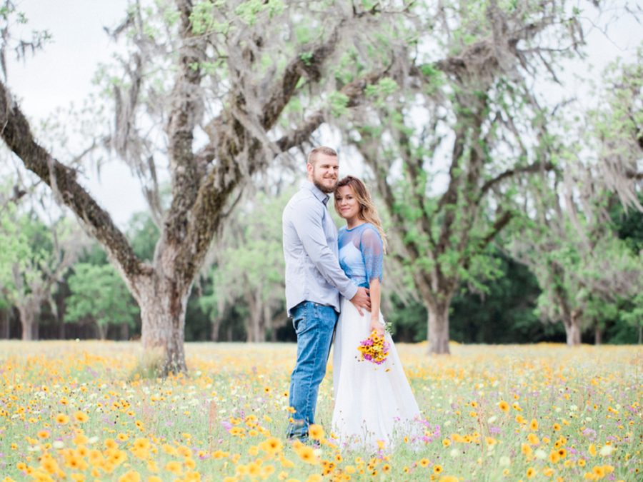 Portrait of man and woman in front of big trees, Engagment posing inspiration, Organic Engagement Pictures in Florida Wildflower Field