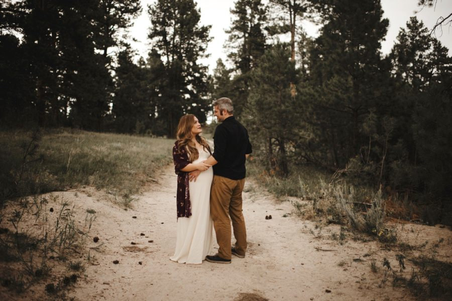 Couple in woods for maternity photos, Moody Sunflower Maternity Session in Colorado
