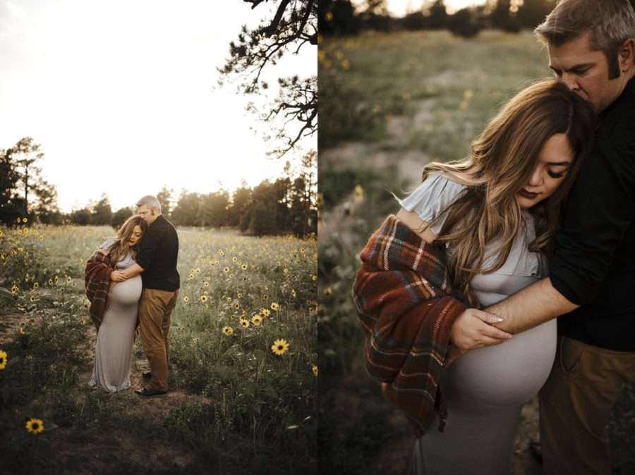 Woman leaning on man during maternity pictures, man kissing woman on head, Moody Sunflower Maternity Session in Colorado