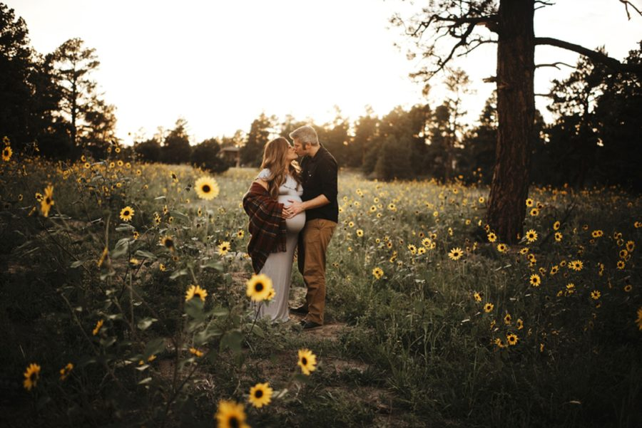 man and woman kissing in golden sun light, Moody Sunflower Maternity Session in Colorado