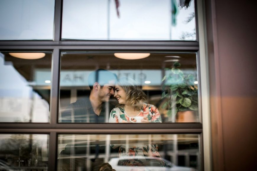 Photo looking in to window of coffee shop, couple sitting inside window of coffee shop, Springtime Engagement Photos in Downtown Olympia