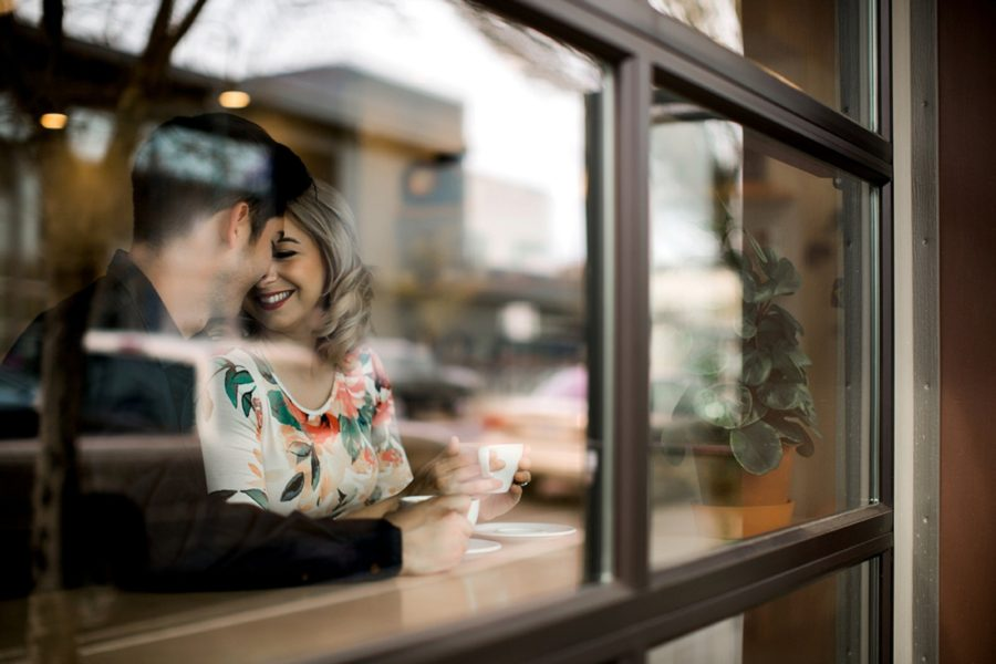 couple drinking coffee together, window reflection of couple together, Springtime Engagement Photos in Downtown Olympia