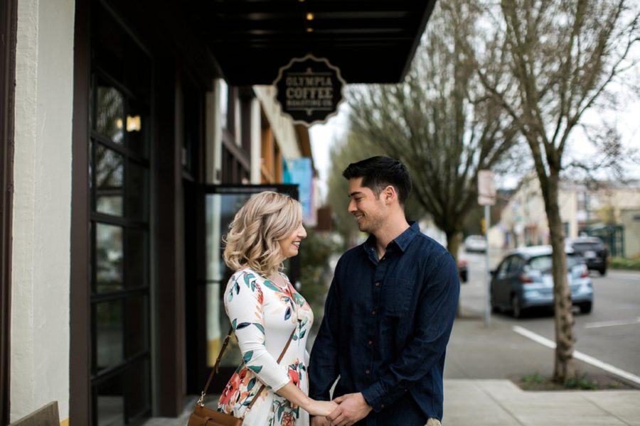 Man and woman outside of coffee shop, Springtime Engagement Photos in Downtown Olympia
