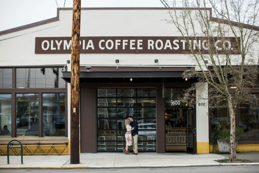 Couple kissing outside coffee shop, Olympia coffee roasting store front, Springtime Engagement Photos in Downtown Olympia